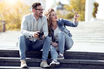 Tourist couple taking photos on street.