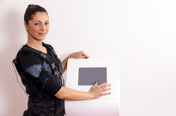Beautiful female trainer standing next to  EMS machine / stimulation