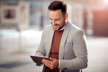 Stylish guy connected on internet with tablet in town.