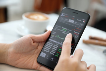Female hand with smartphone trading stock online in coffee shop , Business concept