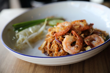 Pad thai with shrimp . Thai food on wood background