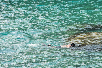Single young boy snorkeling in the tropical sea water on a sunny, warm day