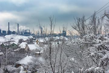 Paesaggio urbano d'inverno con le canne fumarie di una fabbrica