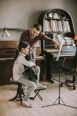 Cute little girl with guitar teacher