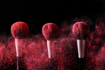 Three brushes for makeup with red make-up shadows in motion on a black background.