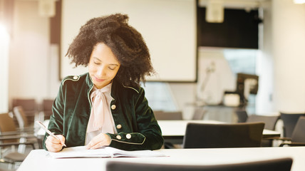 Beautiful latin female student with curly study in light sunny class room