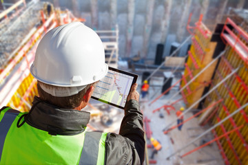 civil engineer or architect on construction site checking schedule with tablet computer