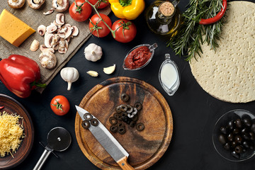 Cutting wooden board with traditional pizza preparation ingredients: cheese, tomatoes sauce, olives, olive oil, pepper, spices. Black texture table background