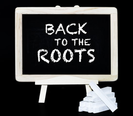 Back to the roots slogan on a blackboard