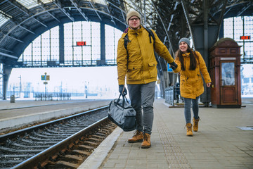 man pull woman to get in time for train