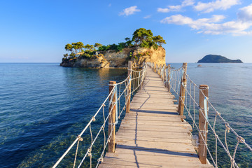 Wooden bridge from Agios Sostis leading to small rocky island. Bay of Laganas, Zakynthos island, Greece.