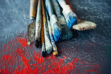 A set of brushes on a colorful colorful background with red blots