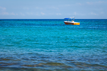 Small orange fishing boat, tourist boat in open water. Tropical turquoise blue sea background.