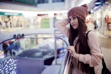 girl in a knitted hat walking in the mall