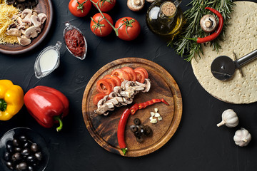 Cutting wooden board with traditional pizza preparation ingredients: cheese, tomatoes, sauce, mushrooms, olive oil, pepper, spices. Black texture table background