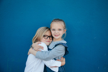 Cute Boy and Girl (Brother and Sister) in glasses hug in front of a blue wall