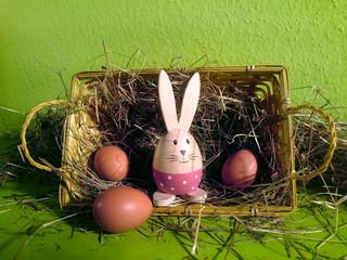 Körbchen mit Heu, braunen Eiern und einem Deko-Häschen mit grünem Hintergrund