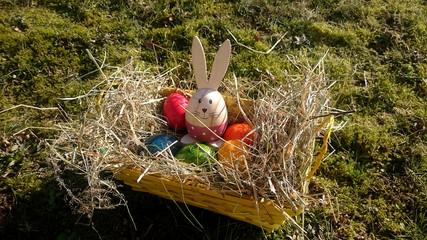 Osterkorb mit bunten Eiern und Deko-Häschen auf der Mooswiese