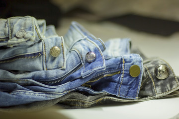 a stack of jeans of different shades lying on each other in the twilight