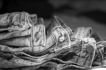 A stack of jeans of different shades lying on each other in black-and-white