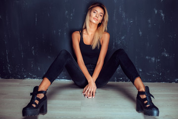 Young stylish blonde in black sitting with legs apart on floor looking at camera.