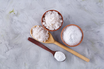 Composition of sea salt in ceramic bowl and spoon for cooking or spa on white background, top view, selective focus
