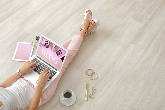 Young beauty blogger using laptop while sitting on floor