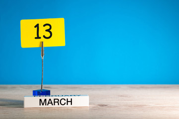 March 13th. Day 13 of march month, calendar on little tag at blue background. Spring time. Empty space for text, mockup