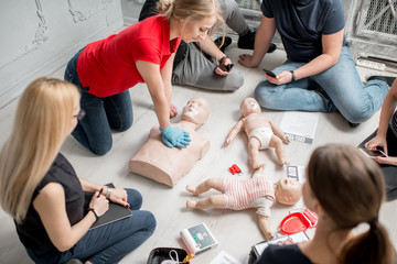 Young woman instructor showing how to make chest compressions with dummy during the first aid group training indoors