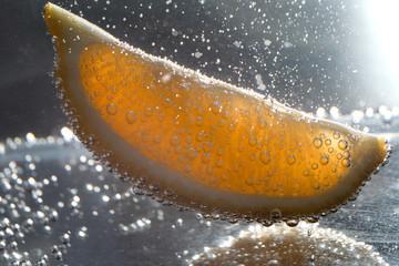 Lemon slice under water with bubbles, closeup