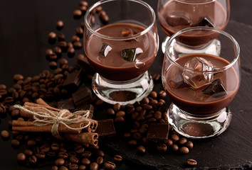 Chocolate, coffee liqueur in glass glasses with ice cubes. With coffee beans, chocolate, cinnamon. On a black background