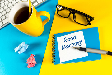 Good morning - is written on small notepad with a cup of morning coffee on rustic wood background with low key scene
