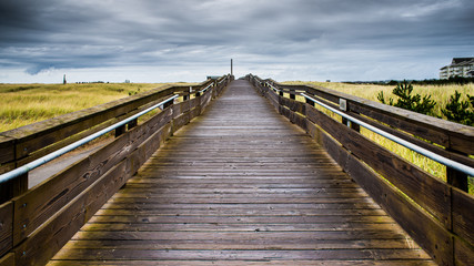 A Wood Bridge Leads To The Horizon By The Horizon Above Large Green Tall Grass Field Under The Stormy Sky And Rolling Clouds In Long Beach Washington