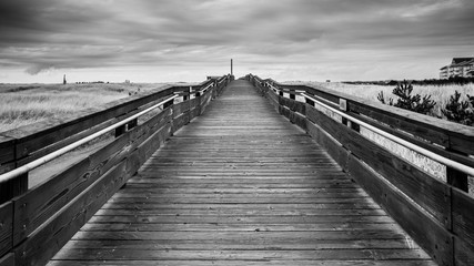 Black And White Of A Wood Bridge That Leads To The Horizon By The Horizon Above Large Green Tall Grass Field Under The Stormy Sky And Rolling Clouds In Long Beach Washington