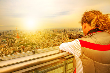 Traveler photographer takes a picture of Tokyo Skyline and Tokyo Tower from atop of Mori Tower in Roppongi Hills complex, Minato District, Tokyo, Japan. Japan travel discovery concept.