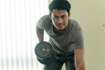 Handsome man playing with dumbbell in gym. Bodybuilder man doing heavy weight exercise with dumbbell in fitness club.