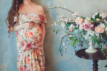 Pregnant woman in a beautiful colorful dress is standing next to a bright bouquet of flowers and holds hands on belly at home interiors. Pregnancy, parenthood, preparation and expectation concept