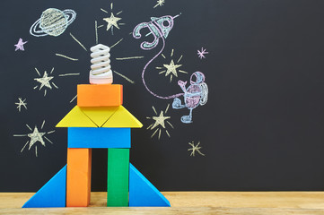 A toy rocket on the background of a chalkboard with a children's drawing of space and an astronaut