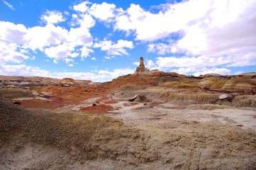 Wide shot of the desert badlands with blue sky and white clouds in the Bisti De Na Zin wilderness in Northern New Mexico