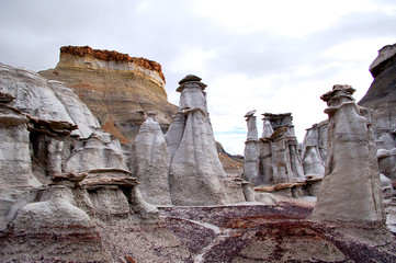 eroded rock formations in desert badlands with grey clouds in the Bisti De Na Zin wilderness in Northern New Mexico