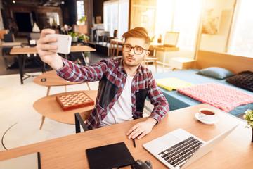 Freelancer man taking selfie at laptop sitting at desk.