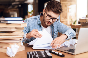 Freelancer man reviewing notes sitting at desk surrounded by books.