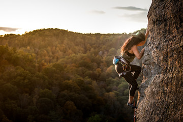 Female climber on a wall climbing at sunset