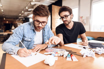 Two freelancer men drawing on paper with pencils at desk.