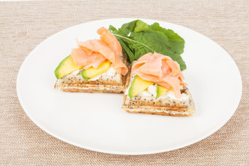 Healthy  breakfast  waffles with avocado and salmon