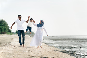 happy family having fun at muddy beach located in pantai remis,Selangor,Malaysia. Family concept