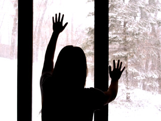 A lonely young girl is putting her hands on a window with snowy background