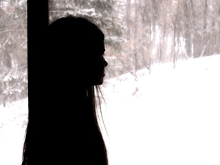 A lonely young girl standing in front of window with snowy background