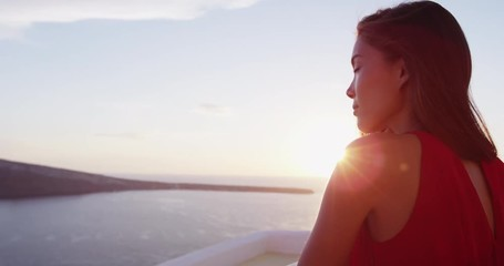 Fototapete - Beautiful woman enjoying the beautiful view of Aegean Sea during sunset. Female tourist is wearing red dress while standing at caldera. She is on her vacation in Santorini.