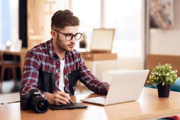 Freelancer man drawing at laptop sitting at desk.